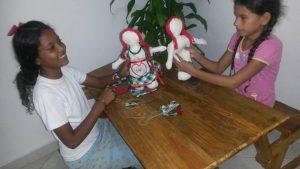Kinderen van Casa Blanca houden zelf gemaakte popjes vast